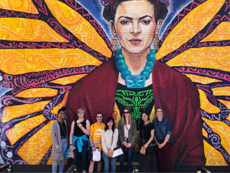 Students pose in front of a mural of Frida Kahlo.