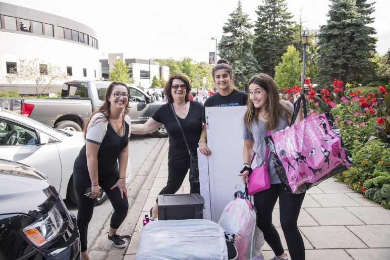 Students move their belongings into a dorm on campus.