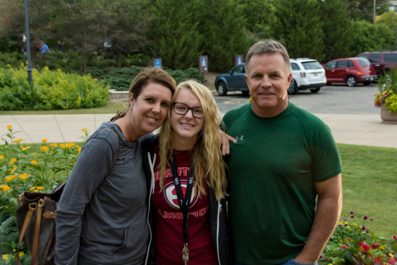 A student poses with her family during move-in 2017.